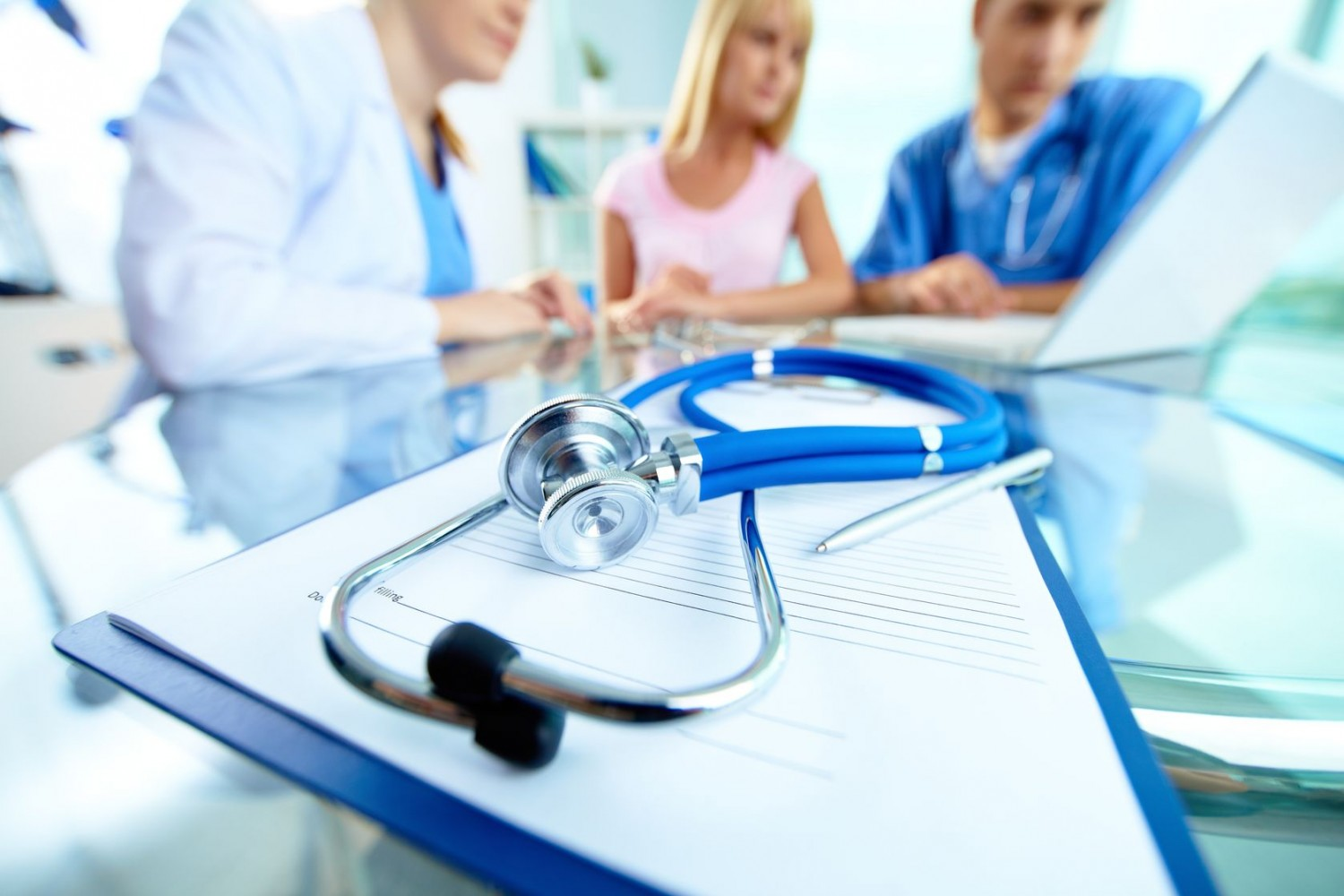 15435918 - close-up of stethoscope and paper on background of doctors and patient working with laptop